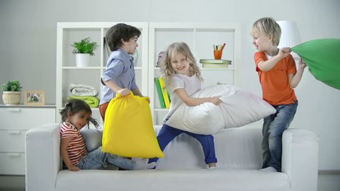 Four kids playing on sofa pillow fighting