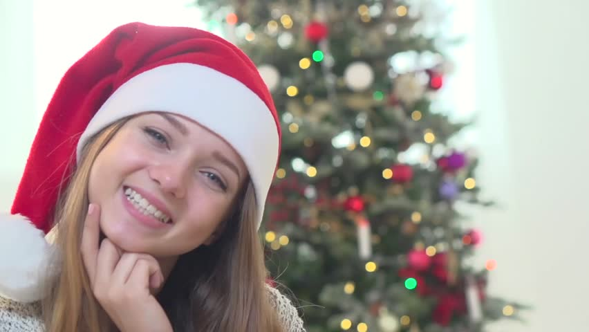 b943d067d5159 Beauty Santa girl portrait. Beautiful Christmas young woman wearing santa  hat having fun at home near the christmas tree. Emotions.