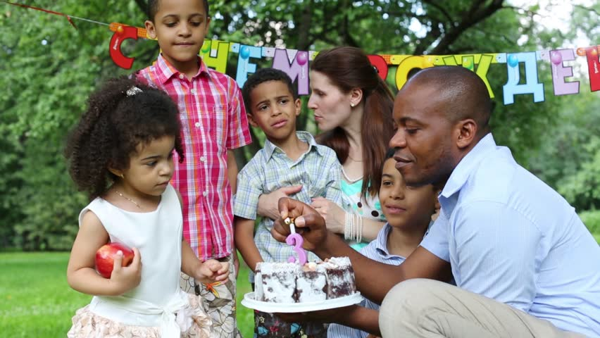 Family Celebrates Third Birthday Of Girl Father Ignites The Candle On Cake Behind