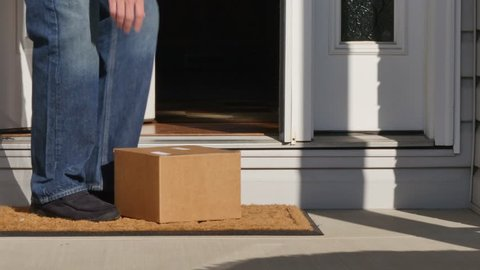 A man picks up a package from outside his front door.