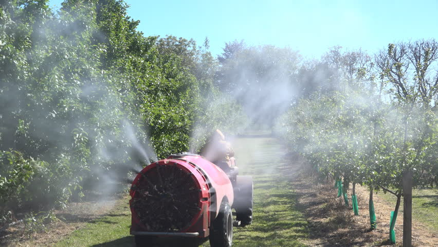 A rear view of an orchard sprayer applying agrochemicals to a commercial apple orchard with an air blast sprayer.