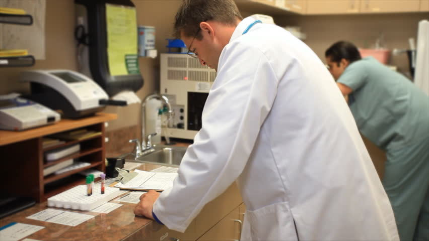 A doctor and a nurse or technician working in a clinics small laboratory.