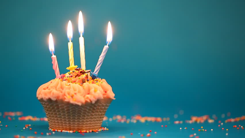 Cupcake With 4 Burning Festive Candles On A Blue Background Stock