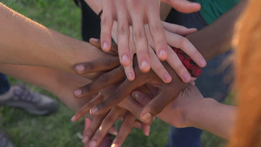 A close-up in slow motion, of hands of all races and colors stacked together one by one in unity and teamwork and then raised. | Shutterstock HD Video #7969738