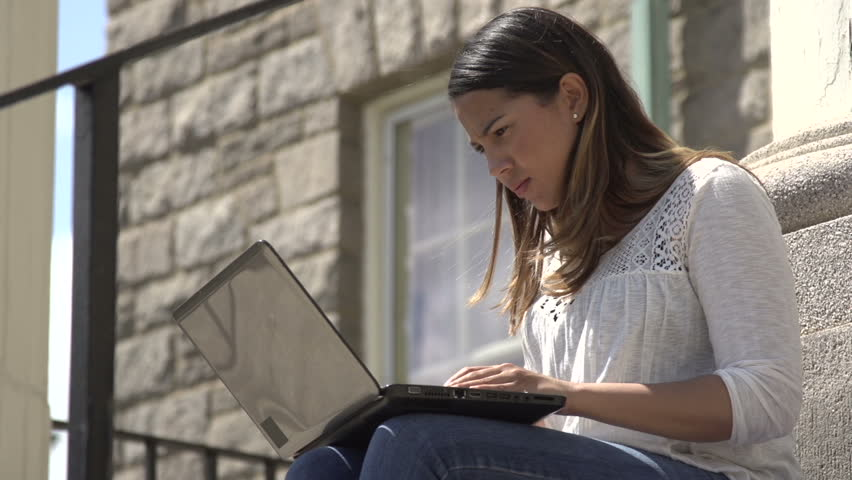 A tilt up to a mid-shot of a hispanic female student, sitting on school steps, using her laptop as other students pass. | Shutterstock HD Video #7973656
