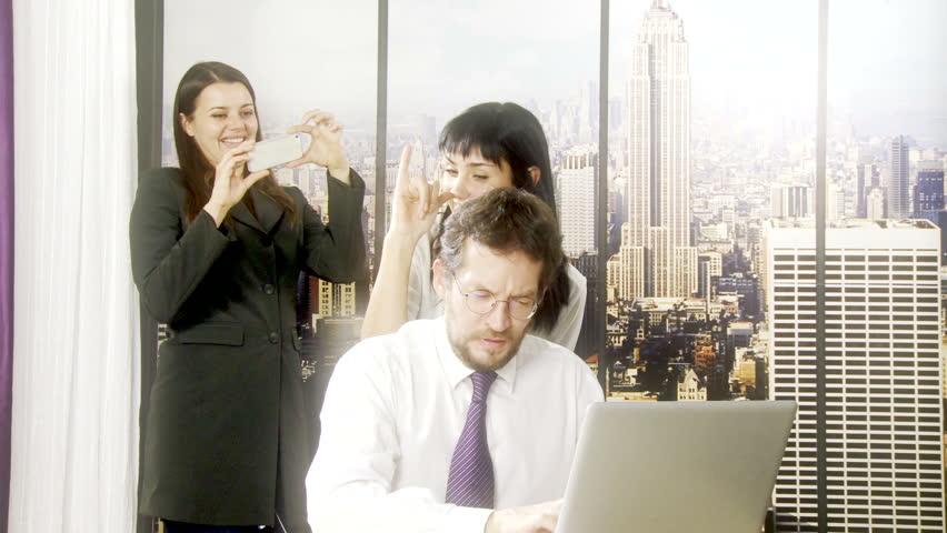 Two women in office teasing man working with computer   Shutterstock HD Video #7988944