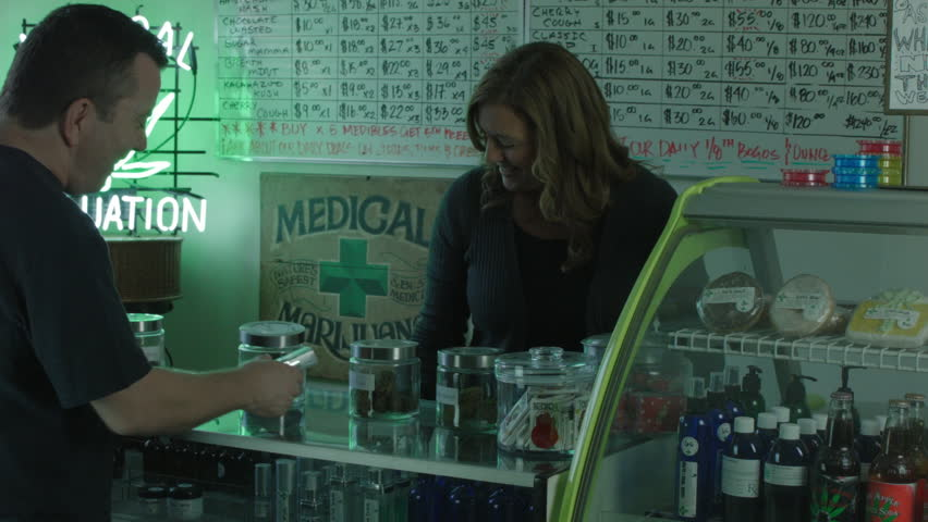 "MEDICAL MARIJUANA DISPENSARY INTERIOR. A FEMALE EMPLOYEE HELPS A MALE CUSTOMER. MEDIUM SHOT / VERSION 2. ALL LABEL ARTWORK WAS CREATED & CLEARED BY ""PROP HEAVEN"" IN BURBANK, CALIFORNIA."