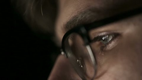 Portrait of a young man with glasses who works at night.  Close up
