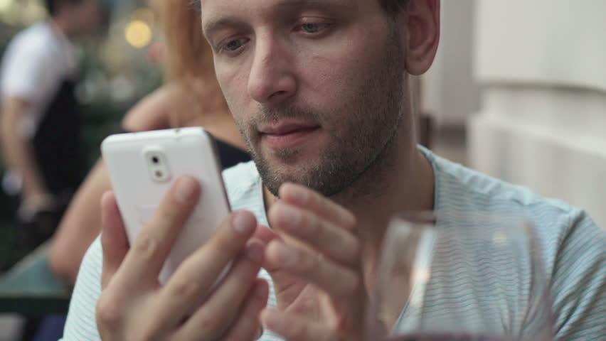 Young man using smartphone and drinking red wine in cafe    Shutterstock HD Video #8016316