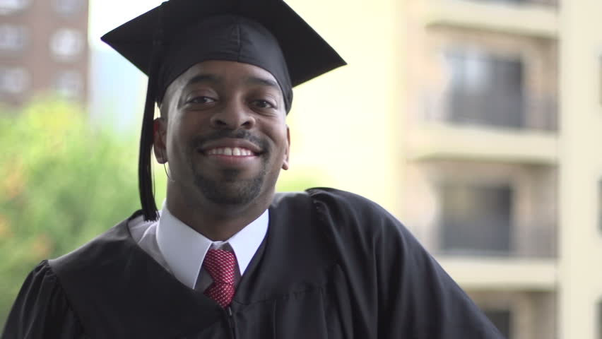 A close-up of a black man, dressed for graduation. He turns to camera and smiles with achievement.