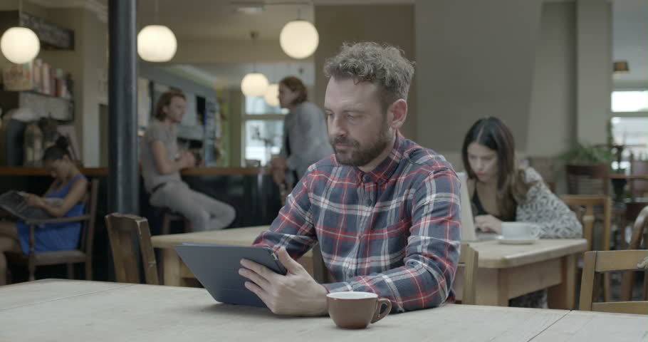 Man using tablet and drinking coffee in pub   Shutterstock HD Video #8044384