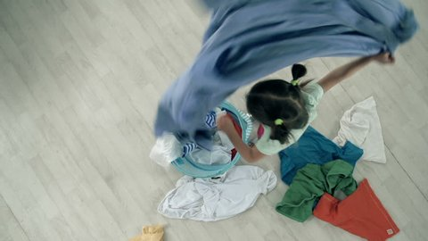 Direct from above shot of little girl throwing out the clothes from buck-basket