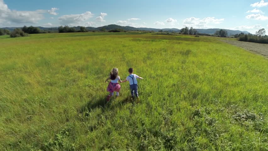 Lovely kids couple running on a grass field. Aerial slow motion shoot of a couple kids holding hands running happily on a grass field free lik a bird