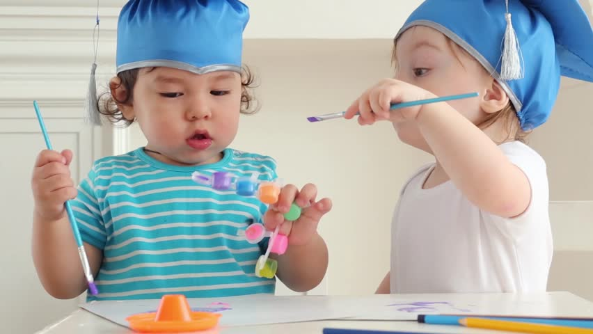 Two cute babies boy and girl in blue graduation hats paint colors on two cute babies boy and girl in blue graduation hats paint colors hd stock footage voltagebd Gallery