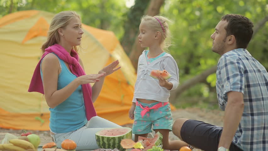 Little Blond Girl Eating A Slice Of Watermelon At The Picnic In Forest Parents