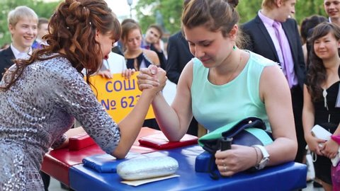 MOSCOW, RUSSIA - JUN 23, 2013: The girls graduates in dresses are arm wrestling on street at Graduate-2013.