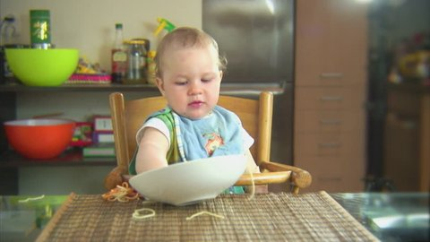Funny child playing with spaghetti and sauce. Scene 5
