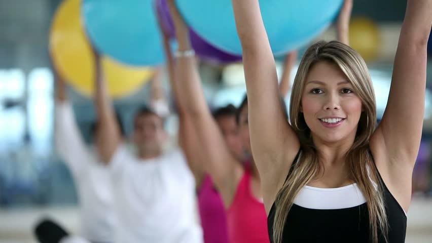 Group of people exercising at the gym with pilates ball