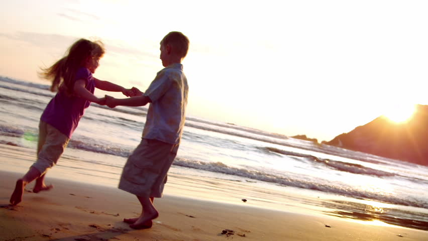 Two children dance on the beach at sunset.
