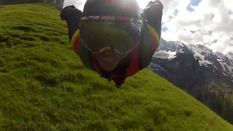 A base jumper in a wingsuit swiftly gliding in the air in a green mountain landscape, POV