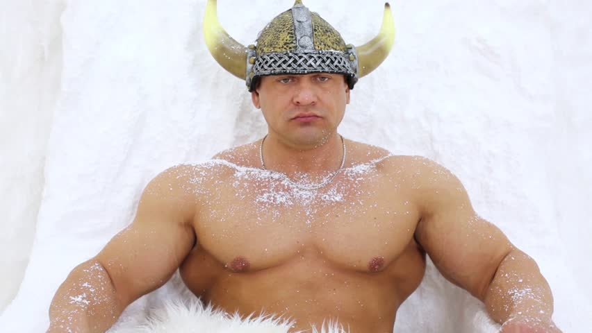 Muscular man dressed in viking costume sits under icy wall on throne.