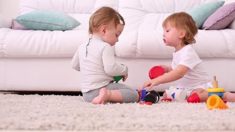 Two pretty girls sit on soft carpet and play with toys near white sofa