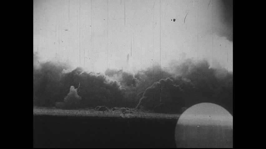 PACIFIC OCEAN 1940s: Atomic bomb explodes on the water causing smoke to rise and debris to fall.  | Shutterstock HD Video #8374246