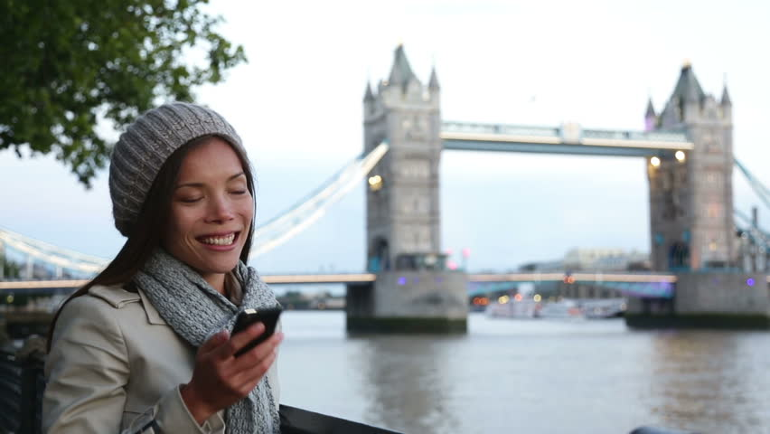 Smartphone - woman talking on cell phone in London in front of Tower  Bridge. Casual