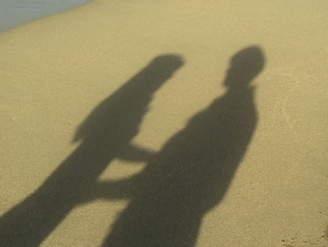 Shadow on beach of two lovers kissing