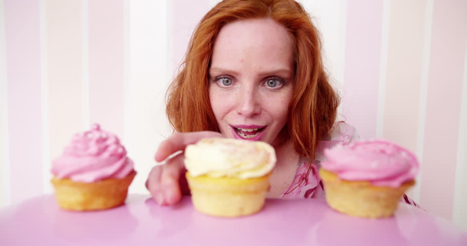 Young red head woman is eating cupcakes in slow motion