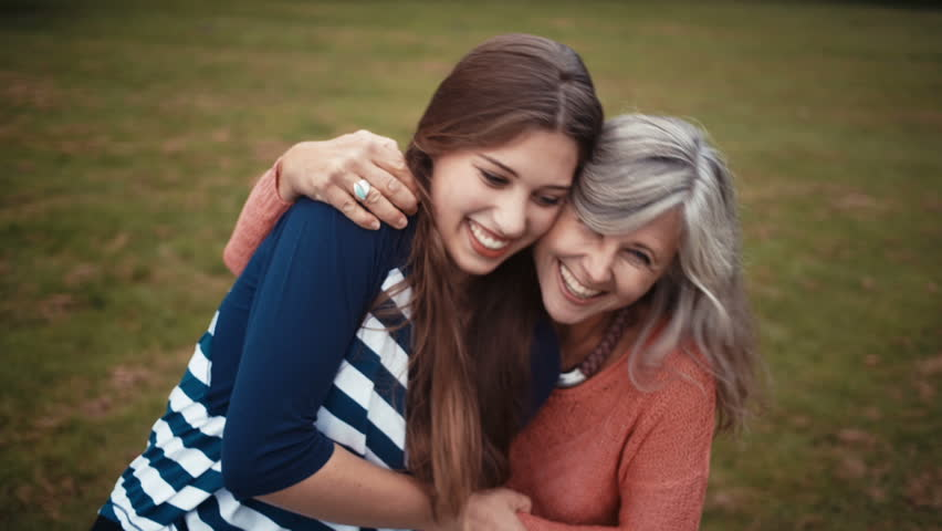 Mother And Daughter Sit In Park Together And Share A Hug