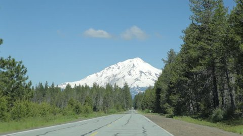 Driving on a 2-lane highway that curves to reveal a long, straight section that leads to a view of Mt Shasta in the background.