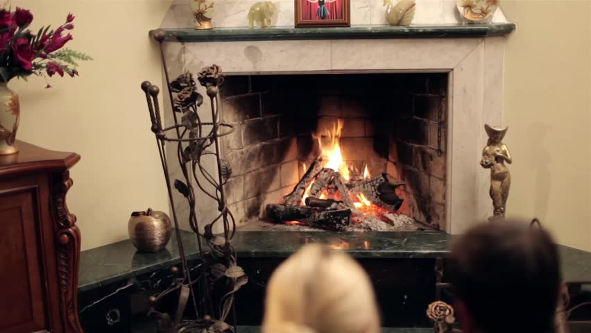 Burning fire in fireplace and two people lying in front of it | Shutterstock HD Video #8400046