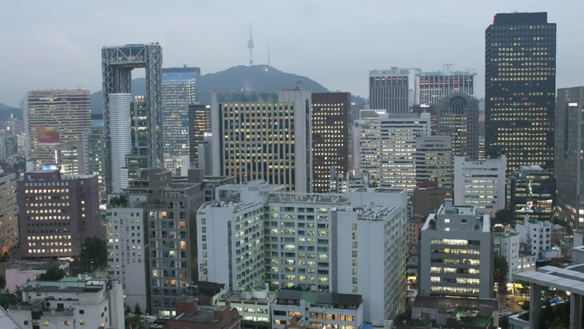 Time lapse cityscape of Seoul at twilight, South Korea. All trademarks and sign boards are blurred.