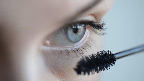 Eye in macro footage of young woman applying mascara on eyelashes