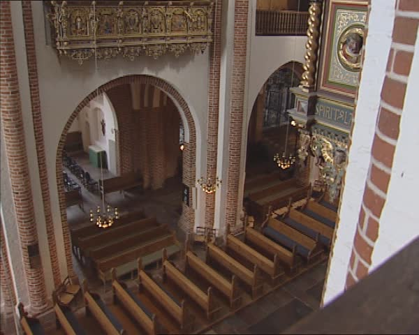ROSKILDE CATHEDRAL, DENMARK - SEPT 2011: Looking down into the nave + tilt up Royal Gallery and the Renaissance Throne of Christian IV (royal pew) high up on the north wall opposite the organ.   Shutterstock HD Video #8550406