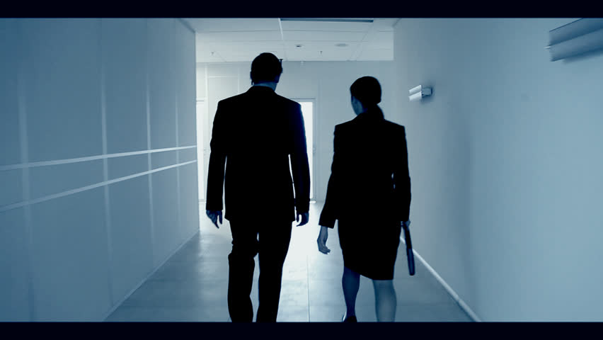 Back view of man and woman going along hallway and coming in light room with chair