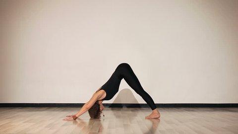 Female performing yoga asanas on the floor. Downward dog and cobra pose