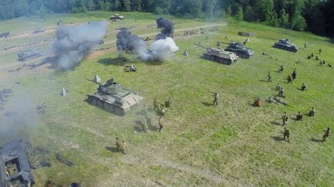 NELIDOVO - JUL 12, 2014: Assault of Soviet army with tanks during reconstruction Battlefield at summer day. Aerial view