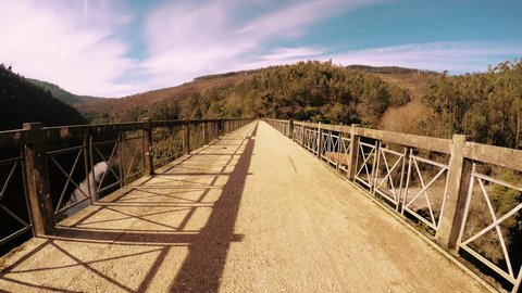 Point of view shot of riding a bicycle in Sever do Vouga, Portugal. Features a wide view of the bike track crossing a bridge.