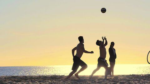 VENICE BEACH, CALIFORNIA - January 2, 2014: Young people playing beach volleyball with ocean as a background. Slow motion.