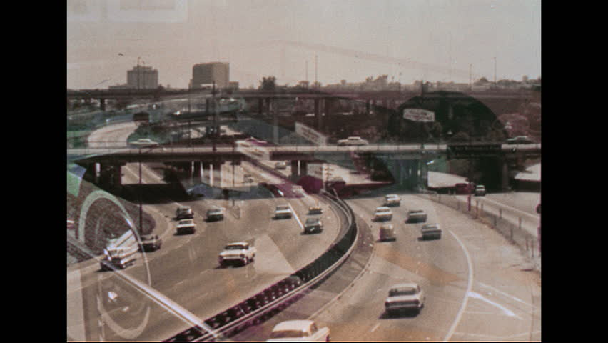 UNITED STATES - CIRCA 1970s: Busy highway. A POV perspective from the hood driving down the highway. Man drives car through a suburban neighborhood. VW Beetle drives through a suburban neighborhood.