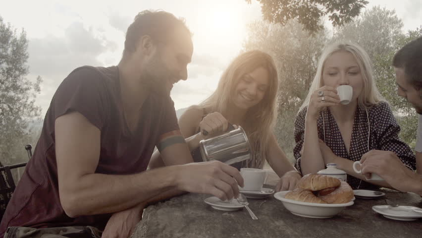Group of four happy men and women friends smile, laugh and drink coffee during italian breakfast on a summer sunny day morning in tuscany, italy with visible sun - slow-motion dolly HD video footage