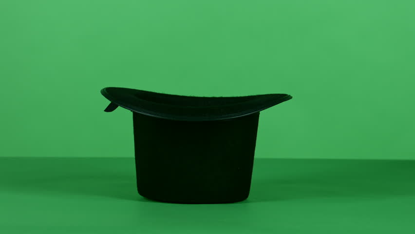 A magician does the tick with an empty black top hat and a magic wand in front of a green screen background