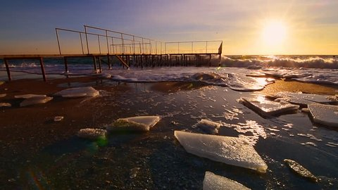 Sunrise ocean dawn wave stormy old pier with ice. 60 fps slow motion