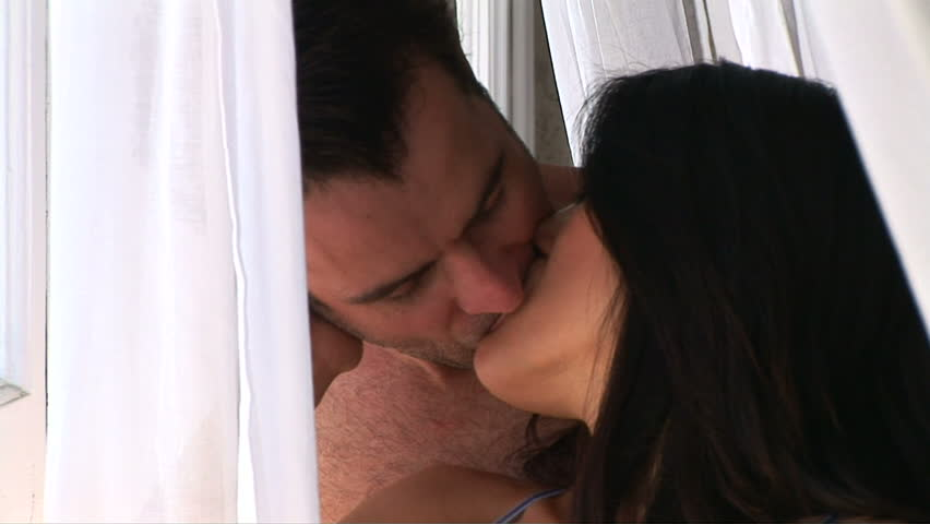 Young romantic couple standing by window kissing with curtain blowing in breeze