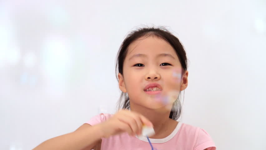 Little girl blows soap bubbles
