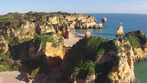 Aerial from rocks and ocean at Praia Tres Irmaos in Alvor the Algarve Portugal