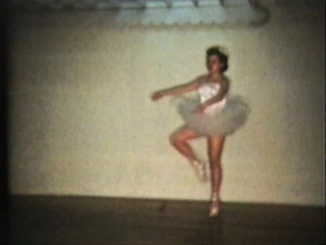 A beautiful teenage girl wearing a pretty princess ballerina dress demonstrates ballet en point at her recital.