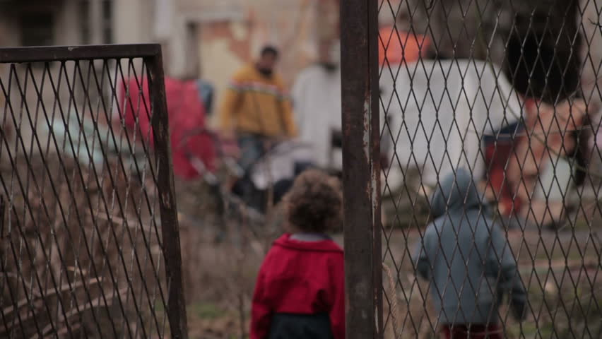 View through the lattice gate on gypsy ruined house. Poor gypsy family in the backyard. Male gypsy preparing firewood and two little kids come home after begging. Father blurred and children in focus.